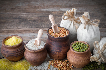 Rustic clay pots filled with rice, green mung, corn, buckwheat and sacks of grain on wooden table. Stock Photo