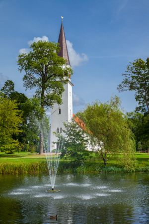 latvia: Lutheran Church of St Berthold and pond in the foreground. Sigulda, Latvia.