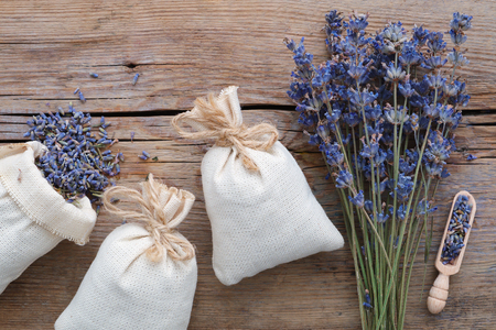 sachets: Dry lavender flowers and sachets on wooden background. Top view. Flat lay.