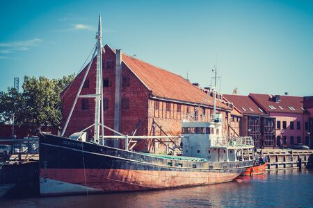 oldtown: LITHUANIA, KLAIPEDA - JULY 20, 2016: boat on Dane river in oldtown of Klaipeda. Lithuania.
