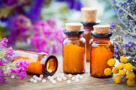 Flessen van homeopathische bolletjes en helende kruiden en bloemen. Homeopathie geneeskunde.