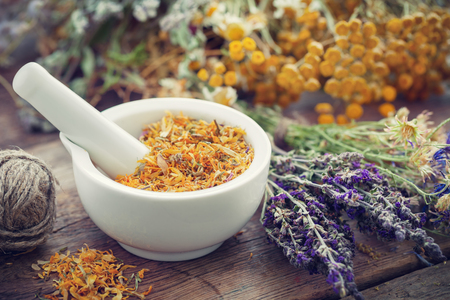 Mortar of dried marigold flowers and healing herbs on wooden plank. Herbal medicine.