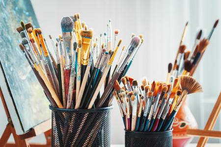 スタジオで功妙な装置: 木製イーゼル、ペイント ブラシ、塗料、パレット、作業アーティスト テーブル上の絵画のチューブ。