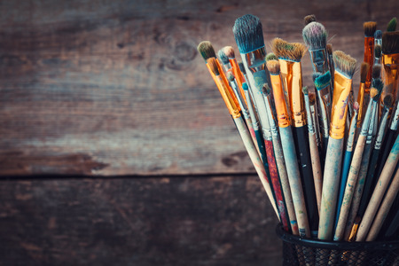 Bunch of paint brushes on wooden background in a artist studio. Copy space for text. Retro toned photo.