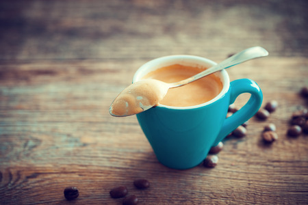 espresso cup: Espresso coffee cup and beans on wooden board. Retro stylized. Stock Photo