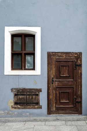 heads old building facade: Vintage wooden entrance door and old windows.