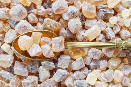 crystalline gold: Caramelized brown sugar in spoon. Cane sugar cubes background. Stock Photo