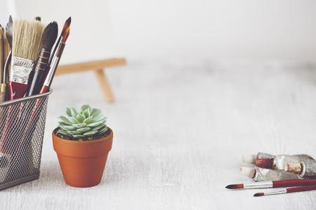 Tavolo da biliardo di moda. Area di lavoro creativa con echeveria succulenta, pennelli, tubi di vernice e tela su cavalletto su sfondo. Archivio Fotografico - 80151070