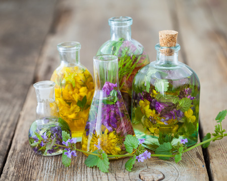 elixir: Bottles of tincture or infusion of healthy herbs on table. Herbal medicine.