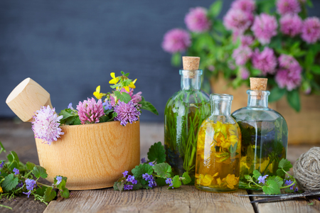 Bottles of tincture or infusion of healthy herbs, healing herbs and wooden mortar of flowers on rustic table. Herbal medicine. Archivio Fotografico