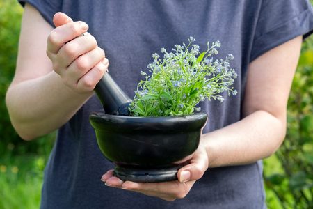 Woman holding a mortar of healing herbs and pestle. Herbal medicine. photo