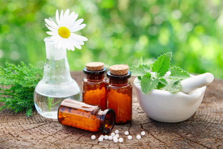 granule: Bottles of homeopathic globules, mortar with mint leaves, daisy flower in flask and juniper bunch. Homeopathy medicine concept. Stock Photo