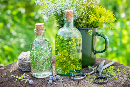 Bottles of tincture or infusion of healing herbs, medicinal herbs in green enameled mug on old stump outside. Herbal medicine.