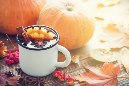 Mulled wine in enameled cup and pumpkins on wooden table with autumn leaves.