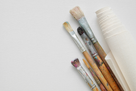 Paintbrushes and roll of artist canvas on white canvas background. Top view. Copy space for text.