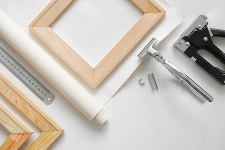 Artist canvas in roll, wooden stretcher bars, canvas stretcher pilers and staple gun. Top view. Stockfoto