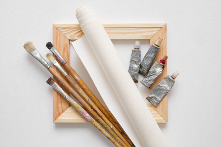 Wooden stretcher bar, paintbrushes, roll of artist canvas and paint tubes on white canvas background. Top view. Stock Photo