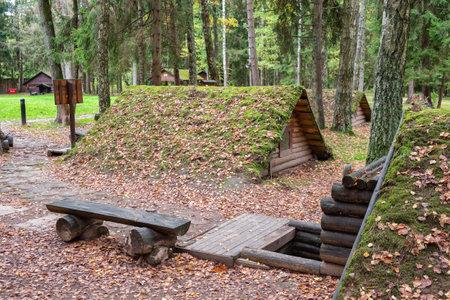 Stankovo village, Belarus - October 08, 2017: vintage wooden dugouts in forest on the territory of military historical complex Partizanen camp in Stankovo, Minsk Region, Belarus.