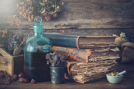 Tinctuurflessen, assortiment droge gezonde kruiden, oude boeken, mortel, curatieve medicijnen. Kruidenmedicijn. Retro stijl.