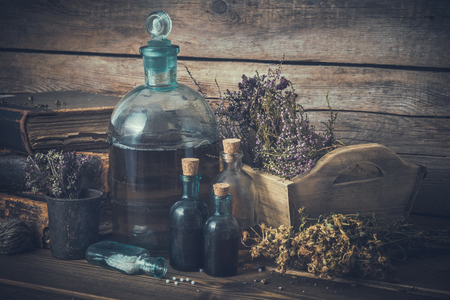 Tincture bottles, vial of homeopathy globules, old books, dry healthy herbs and curative drugs. Herbal and homeopathic medicine.