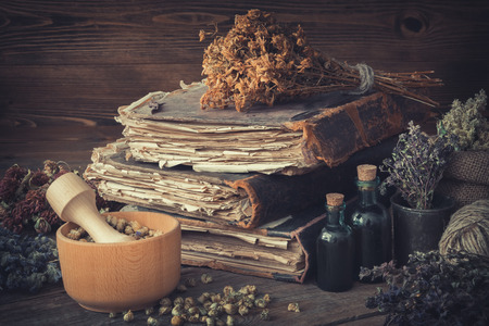 Tincture bottles, bunches of dry healthy herbs, stack of antique books, mortars, sack of medicinal herbs. Herbal medicine.