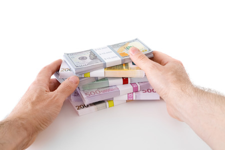 Hands with banknotes of dollars and euro on white.