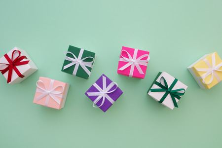 Gift boxes with ribbons on pastel green background. Top view, flat lay. Copy space for text. Фото со стока