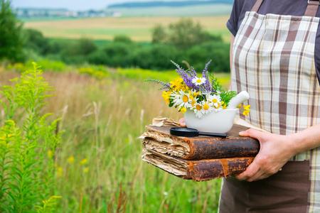 Mujer sosteniendo en sus manos libros antiguos, un mortero y lupa. Herbolario recoge plantas medicinales en un prado.