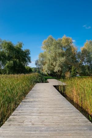 Wooden ecological footpath, footbridge over the beautiful lake. Foto de archivo