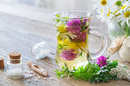 Two glass mugs of healthy herbal tea or infusion, bottles of homeopathic globules and medicinal herbs. Homeopathy and herbal medicine. Stock Photo