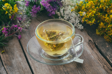 Glass tea cup with tea bag of healthy herbal tea and bunches of medicinal herbs
