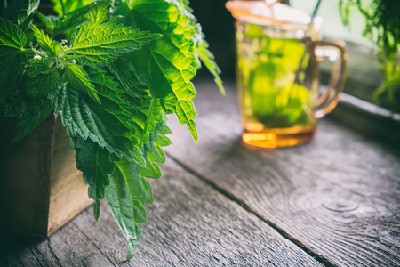 Bunch of a nettle plants in a wooden box  and glass of healthy nettle tea not in focus on old wooden table in a retro village house. Stock Photo