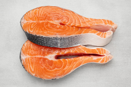 Fresh raw salmon fish steaks on natural stone