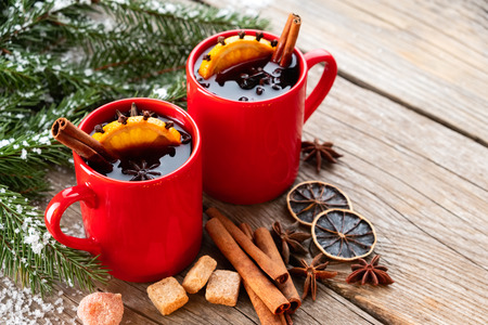 Red mugs of hot mulled wine with spices and citrus fruits