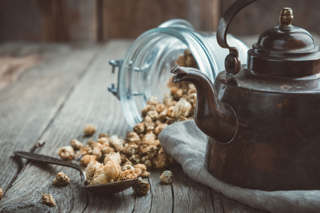 Vintage teapot and glass of dry healthy chamomile buds on wooden table.