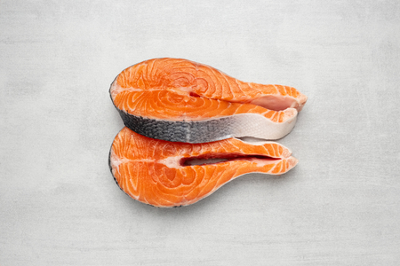 Two raw salmon fish steaks on natural stone Stock Photo