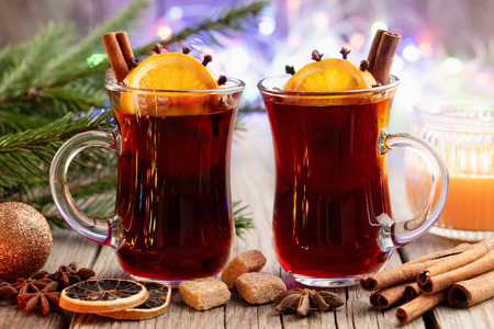 Glass mugs of hot mulled wine with spices and citrus fruits