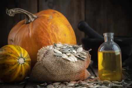 Pumpkin seeds oil bottle, two pumpkins, bag of seeds and mortar Stock Photo