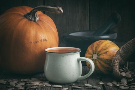 Cup of pumpkin juice, pumpkins, canvas sack of pumpkins seeds  and mortar on wooden table.