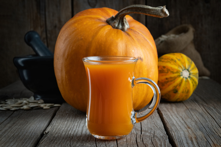Glass cup of fresh pumpkin juice, pumpkins on table, mortar and sack of seeds