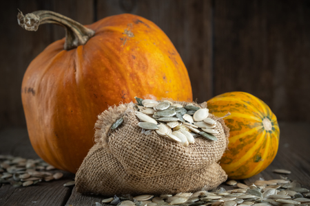Canvas bag of pumpkins seeds and two pumpkins on wooden table. Stock Photo