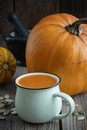 Cup of pumpkin juice, pumpkins and black mortar on wooden table.