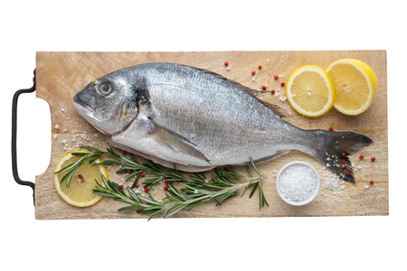 Fresh dorado fish with lemon slices, salt and rosemary on cutting board. Top view, isolated on white. Stock Photo