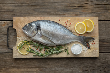 Fresh dorado fish with lemon slices, salt and rosemary on wooden cutting board. Top view.