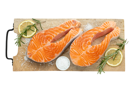 Two raw salmon fish steaks with lemon slices, salt and rosemary on cutting board. Top view, isolated on white.