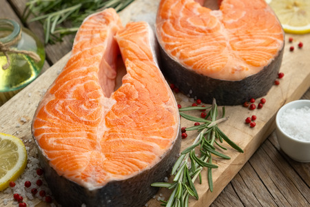 Two raw salmon fish steaks with lemon slices, salt and rosemary on cutting board. Stock Photo
