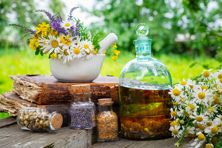 Mortar of healing herbs, bottles of healthy essential oil or infusion and dry medicinal herbs, old books and bunch of chamomile plant. Herbal medicine. Stock Photo - 115238785