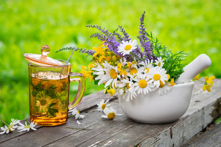 Healthy herbal tea cup, mortar of medicinal herbs on wooden board outdoors. Stock Photo