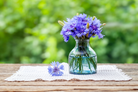 Summer bouquet of blue cornflower on wooden board outdoors with copy space. Stock Photo - 115238798
