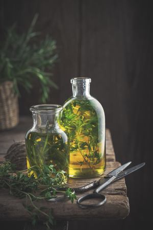 Bottles of thyme and rosemary essential oil or infusion and scissors on old wooden table. Stock Photo